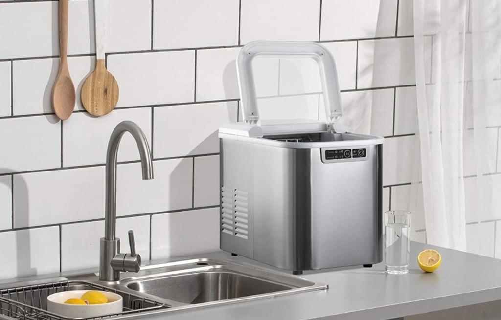 Una máquina de hielo pequeña y potente para el hogar, colocada sobre una encimera de color gris.