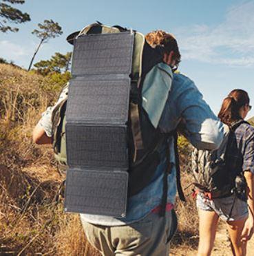 Panel solar portátil para el camping colgado de una mochila que lleva un hombre que camina en mitad de un sendero soleado.